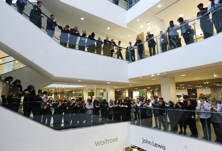 Workers, known as partners at the John Lewis Partnership, celebrate after the announcement of their annual profit related bonus, at their fl