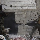Free Syrian Army fighters return fire after what they say was during clashes with forces loyal to President Bashar al-Assad in Deir al-Zor M