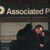 A man looks down at his smartphone as he walks past the offices of the Associated Press in Manhattan, New York May 13, 2013. REUTERS/Adrees