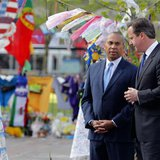 British Prime Minister David Cameron (R) visits a memorial to the victims of the Boston Marathon bombings in Copley Square with Massachusett