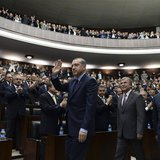 Turkey's Prime Minister Tayyip Erdogan (C) greets members of parliament from his ruling AK Party (AKP) during a meeting at the Turkish parli