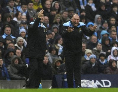 Manchester City's manager Roberto Mancini (L) and his assistant David Platt instruct their team during their FA Cup soccer match against Man