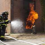 Firefighters put out a live fire during an experiment on Governors Island, in New York, July 3, 2012. REUTERS/Andrew Burton
