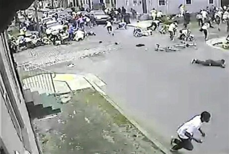 A still image taken from security camera video released by the New Orleans Police Department (NOPD) shows a gunman (bottom R) running away a
