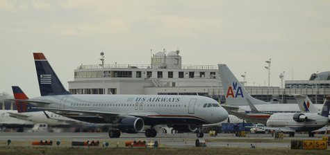 US Airways jets taxi past a parked American Airlines jet (C) at Reagan National Airport in Washington February 28, 2013. REUTERS/Gary Camero