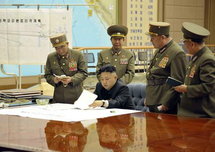 North Korean leader Kim Jong-un (C) presides over an urgent operation meeting on the Korean People's Army Strategic Rocket Force's performan