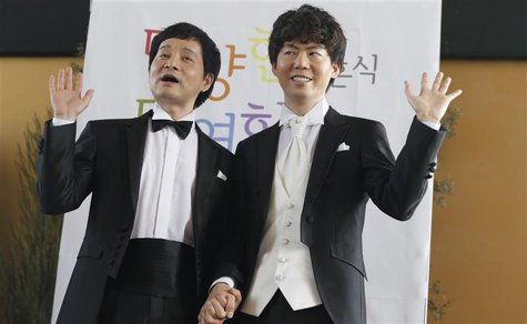 Gay South Korean film director Kim Jho Gwang-soo (L) and his partner Kim Seung-hwan pose during a news conference in Seoul May 15, 2013. REU
