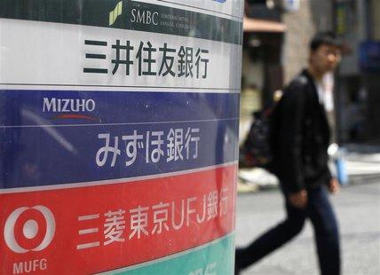 A man walks past a signboard of Japan's three mega banks, Sumitomo Mitsui Banking Corporation (top), Mizuho Bank (C) and Bank of Tokyo-Mitsu