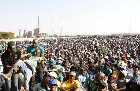An unruly AMCU member (L) is removed from a gathering as other members are addressed by their leaders during a strike at Lonmin's Marikana p