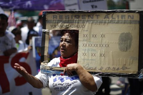 Rosa Ayala carries a Resident Alien placard during the International Workers Day and Immigration Reform March on May Day in Los Angeles, Cal