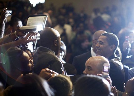 A churchgoer (L) tries to hand a Bible to US Democratic presidential candidate Barack Obama (R) to autograph as he greet worshippers followi
