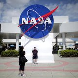 Tourists take pictures of a NASA sign at the Kennedy Space Center visitors complex in Cape Canaveral, Florida April 14, 2010. REUTERS/Carlos
