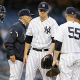 New York Yankees starting pitcher Phil Hughes heads to the dugout after being removed by Yankees manager Joe Girardi during the first inning
