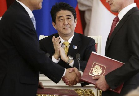 Japan's Prime Minister Shinzo Abe applauds during a signing ceremony after the talks with Russia's President Vladimir Putin at the Kremlin i