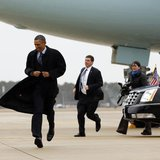 U.S. President Barack Obama runs to greet well-wishers upon his arrival in Newport News, Virginia February 26, 2013. REUTERS/Kevin Lamarque