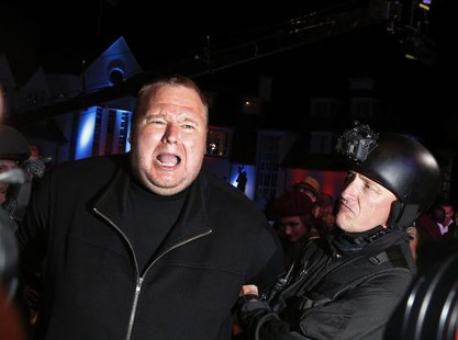 "An actor in police costume mock-arrests Megaupload founder Kim Dotcom (L) as he launches his new file sharing site ""Mega"" in Auckland Januar"