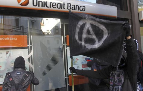 Students paint on the front of a Unicredit bank during a protest against government budget cuts in Milan December 12, 2012. REUTERS/Stringer