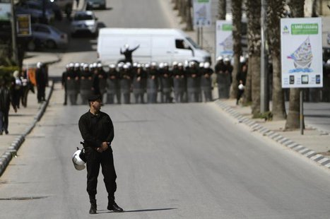 Palestinian police officers block the road to prevent Palestinian demonstrators from marching towards the Jewish settlement of Beit El March