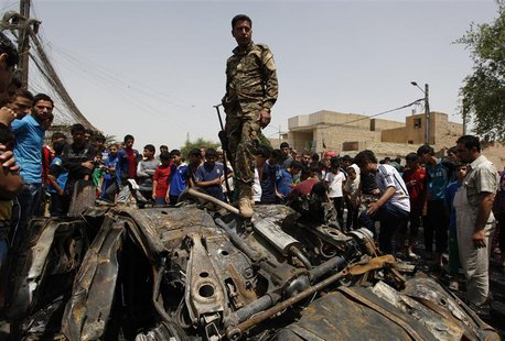 An Iraqi soldier steps over wreckage of a car bomb at the site of a car bomb attack in Baghdad's Sadr City May 16, 2013. REUTERS/Mohammed Am