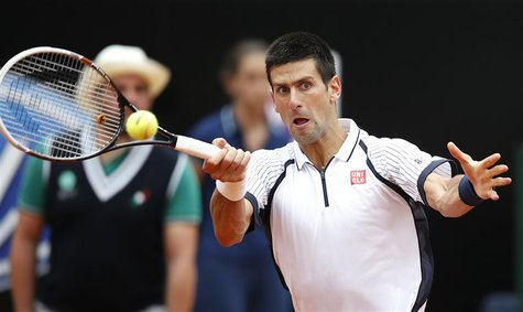 Novak Djokovic of Serbia hits a return to Alexandr Dolgopolov of Ukraine during their men's singles match at the Rome Masters tennis tournam