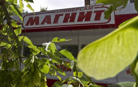 Leaves frame the front of a grocery store owned by retailer Magnit in Moscow July 24, 2012. REUTERS/Maxim Shemetov