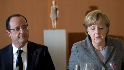 German Chancellor Angela Merkel (R) and French President Francois Hollande arrive for a dinner with representatives of the European Round Ta
