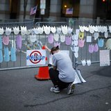 A woman kneels and cries in front of a memorial to the Boston Marathon bombings victims, at the barricades surrounding the scene in Boston,
