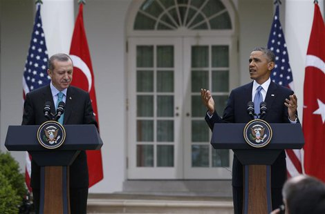 U.S. President Barack Obama (R) reacts to rain starting to fall, as he and Turkish Prime Minister Recep Tayyip Erdogan hold a joint news con