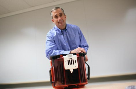 Intel Chief Operating Officer Brian Krzanich poses with a Front Opening Unified Pod, a transport unit for computer chip wafers, with each FO
