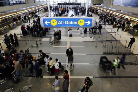 Passengers with their baggage move through the check-in area of the Tom Bradley International Terminal at Los Angeles International Airport