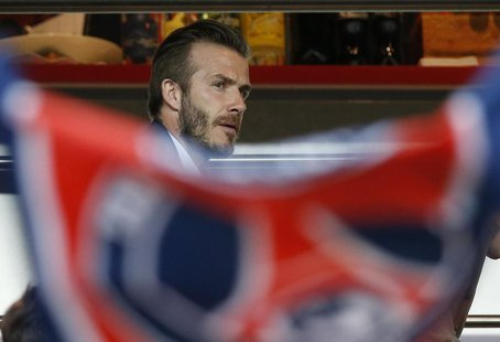 Paris Saint-Germain's David Beckham takes his seat in the stands during their French Ligue 1 soccer match against Valenciennes at the Parc d