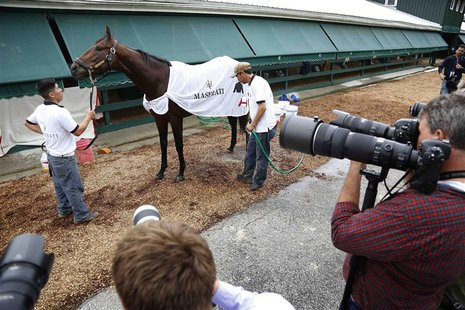 Photographers keep an eye on Kentucky Derby winner Orb after a workout in preparation for the upcoming 138th running of the Preakness Stakes