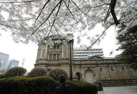 A man takes pictures in front of the Bank of Japan building in Tokyo, March 29, 2013. REUTERS/Yuya Shino