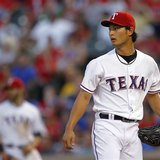 Texas Rangers starting pitcher Yu Darvish looks to the outfield after giving a hit to Detroit Tigers' Victor Martinez to score a run in the