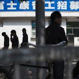 People walk past a closed job centre of Foxconn factory in the township of Longhua in Shenzhen, Guangdong province February 21, 2013. REUTER