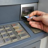A man uses a traditional automated teller machine (ATM) in Bucharest May 17, 2013. REUTERS/Bogdan Cristel
