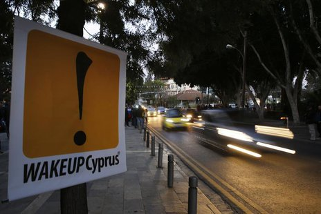 Vehicles speed past a sign placed by anti-Troika protesters outside the parliament in Nicosia March 24, 2013. REUTERS/Yannis Behrakis