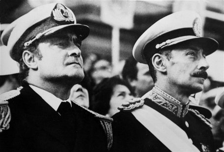 "Argentine Army General Jorge Videla (R), leader of the 1976 military coup that began the seven-year ""Dirty War,"" stands next to junta member"