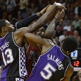 Miami Heat's LeBron James (C) is defended by Sacramento Kings' Tyreke Evans and John Salmons (R) during the first half of their NBA basketba