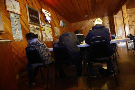A group of illegal immigrants, who handed themselves in to U.S. Border Patrol, sit in a restaurant in Encino, Texas March 29, 2013. REUTERS/