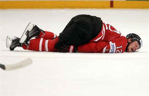 Canada's Eric Staal (R) lies injured on the ice during their 2013 IIHF Ice Hockey World Championship quarter-final match against Sweden at t