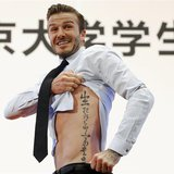 Former England captain David Beckham shows his tattoo after he was asked to by students at Peking University during his visit in Beijing in