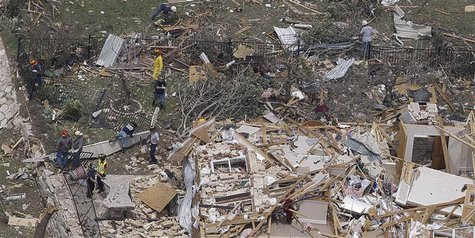 Rescue workers go through the debris of a house left flattened by a tornado in this aerial photograph taken over Granbury, Texas on May 16,