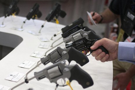 A man holds a gun in the exhibit hall of the George R. Brown Convention Center, the site for the National Rifle Association's (NRA) annual m
