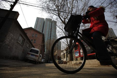 A woman rides her bicycle along an alley next to a residential compound in central Beijing, March 22, 2013. REUTERS/Petar Kujundzic