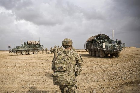 U.S. Army soldiers with Charlie Company, 36th Infantry Regiment, 1st Armored Division head back to their vehicles at the end of a mission ne