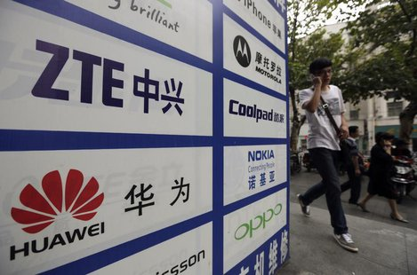 A man walks past an advertisement board showing the logos of Huawei and ZTE on it, outside a mobile phone repair shop in Wuhan October 11, 2