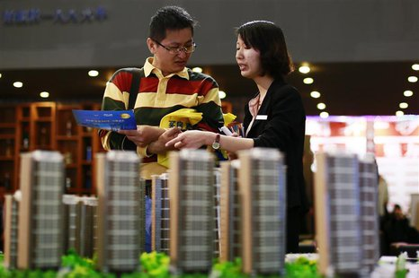 A salesperson (R) talks to a customer behind models of a residential compound at a real estate exhibition in Wuxi, Jiangsu province May 18,