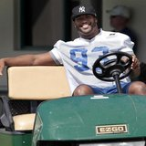 Injured Indianapolis Colts defensive end Dwight Freeney smiles as he drives a golf cart before practice at the Miami Dolphins training facil