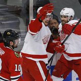 Detroit Red Wings' Brendan Smith (C) celebrates his goal with teammate Henrik Zetterberg as Chicago Blackhawks' Patrick Sharp (L) skates pas